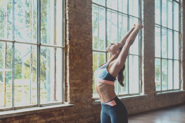 woman doing chest breast stretch in yoga studio