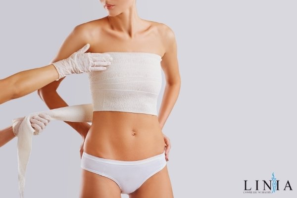 patient in bandages with breast implants getting doctor check over time